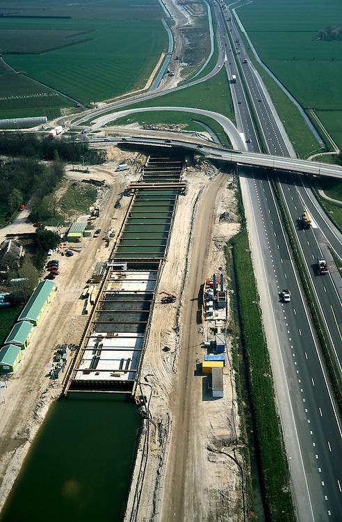 Nederland, Gelderland, Meteren, 01-04-2002;  aanleg Betuweroute, parallel aan A15: de toekomstige spoorlijn wordt verdiept aangelegd, zodat de lokale weg er over heen kan; de bouwput is uitgegraven en voorzien van damwanden, door het grondwater staat deze onder water, er wordt met onderwaterbeton gewerkt; oorspronkelijk stonden er op deze lokatie boerderijen (zie reguliere foto's); ook luchtfoto van de voltooide bouw; bouw, transport, infrastructuur, verkeer en vervoer, mobiliteit, Betuwlijn, planologie; zie ook andere foto's van deze lokatie; deel van de serie Panorama Nederland <br /> luchtfoto (toeslag); aerial photo (additional fee required); .foto Siebe Swart / photo Siebe Swart
