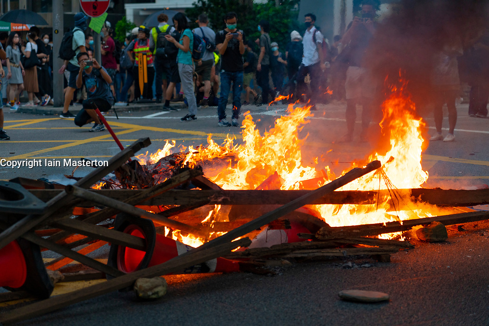 Hong Kong. 4 October 2019. Large gathering of pro- democracy supporters evening in Hong Kong Central District. Protestors angry with Chief Executive Carrie Lam's use of Emergency Powers to ban the wearing of masks during protests. March proceeded peacefully towards Wanchai district. Pic. Fires set on roads in Central before march.  Iain Masterton/Alamy Live News.