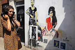 © Licensed to London News Pictures. 23/07/2021. LONDON, UK.  A woman passes a mural of Amy Winehouse by street artist bambi in Bayham Street in Camden Town on the tenth anniversary of the late singer's death.  Photo credit: Stephen Chung/LNP