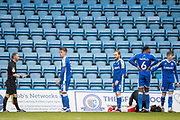 John Busby (Referee) awarded a red card to Connor Ogilvie, Defender with Gillingham (3) who remains on the pitch in disbelief while Josh Eccles, Defender with Gillingham (17) & Jack Tucker, Defender with Gillingham (5) talk with Andy Bennett (Assistant Referee) and Jay Matete, Midfielder with Fleetwood Town FC (36) is injured and receives treatment during the EFL Sky Bet League 1 match between Gillingham and Fleetwood Town at the MEMS Priestfield Stadium, Gillingham, England on 24 October 2020.