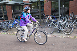 Woman riding her bike from a works bike shed,