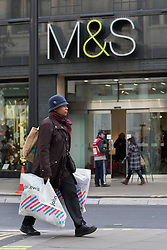 © licensed to London News Pictures. London, UK 06/11/2012. People walking past a M&S store in Oxford Street on 06/11/12. Marks & Spencer has reported a 10pc fall in profits. Photo credit: Tolga Akmen/LNP