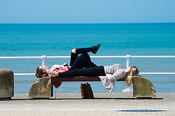 © London News Pictures. 05/05/2016. Aberystwyth, UK. Two young women lying on a seaside bench  enjoying the warm spring sunshine in Aberystwyth Wales.  The temperature is forecast to rise over the coming days,  as a plume of warm air moves in from the near continent,  reaching the low 20's centigrade by the weekend. Photo credit: Keith Morris/LNP