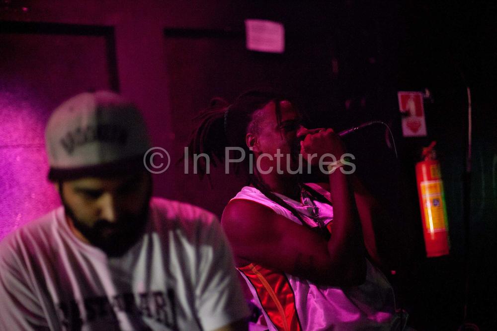 Male Brazilian singer with dreadlocks and microphone, pink lighting in a club. Digital Dubs dub reggae dancehall soundsystem at Leviano Bar, Lapa, Rio de Janeiro, Brazil