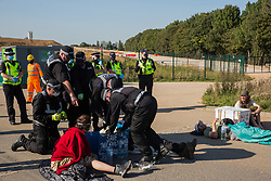 West Hyde, UK. 14th September, 2020. Officers from a Hertfordshire Police cutting team work to remove environmental activists from HS2 Rebellion using lock-on arm tubes to block a gate to the South Portal site for the HS2 high-speed rail link. Anti-HS2 activists blocked two gates to the same works site for the controversial £106bn rail link, one remaining closed for over six hours and another for over nineteen hours.