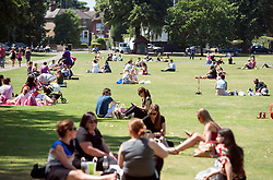© Licensed to London News Pictures. 22/07/2014. Richmond, UK. People sit on Richmond Green.  People enjoy the sunny hot weather on the banks of the River Thames at Richmond, Surrey, today 22th July 2014. Photo credit : Stephen Simpson/LNP