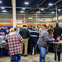 Harrisburg, PA / USA - January 9, 2020: People use stand up tables to eat while at the PA Farm Show in the food court areas. The food courts become very crowded at the annual event.