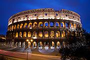 Full view of the Roman Coliseum at night with a dark blue sky and Via dei Fori Imperiali below, Rome, Lazio, Italy.