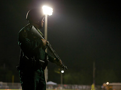 August 18, 2018 - Wellington, Florida, U.S. - A police man stands guard as Trauma Hawk lands on the field at Palm Beach Central High School to transports a shooting victim. Two adults were shot Friday night at a football game between Palm Beach Central and William T. Dwyer high schools, authorities said. The gunfire sent players and fans screaming and stampeding in panic during the fourth quarter of the game at Palm Beach Central High School in Wellington, Florida on August 17, 2018. (Credit Image: © Allen Eyestone/The Palm Beach Post via ZUMA Wire)