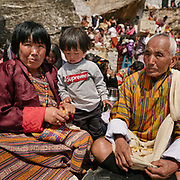 Layap grandfather and grandmother with their grand daughter wearing an Supreme shirt. The Tshechu of the Gasa monastery on the road leading to Laya. Tshechu are annual religious Bhutanese festivals held in each district on the tenth day of a month of the lunar Tibetan calendar. Tshechus are large social gatherings, which perform the function of social bonding among people of remote and spread-out villages.