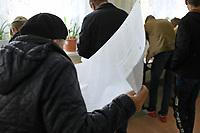 Kobylin Borzymy, woj podlaskie, 13.10.2019. Glosowanie w Obowodowej Komisji Wyborczej nr 2. W wyborach 2015 roku na PiS glosowalo tutaj 86% wyborcow N/z najwiecej wyborcow glosowalo po porannej mszy swietej w miejscowym kosciele; wyborca przeglada liste kandydatow na karcie do glosowania fot Michal Kosc / AGENCJA WSCHOD