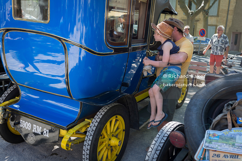 A child admired a visiting vintage car in the centre of a French village, during a three-day rally journey through the Corbieres wine region, on 26th May, 2017, in Lagrasse, Languedoc-Rousillon, south of France. Lagrasse is listed as one of France's most beautiful villages and lies on the famous Route 20 wine route in the Basses-Corbieres region dating to the 13th century.