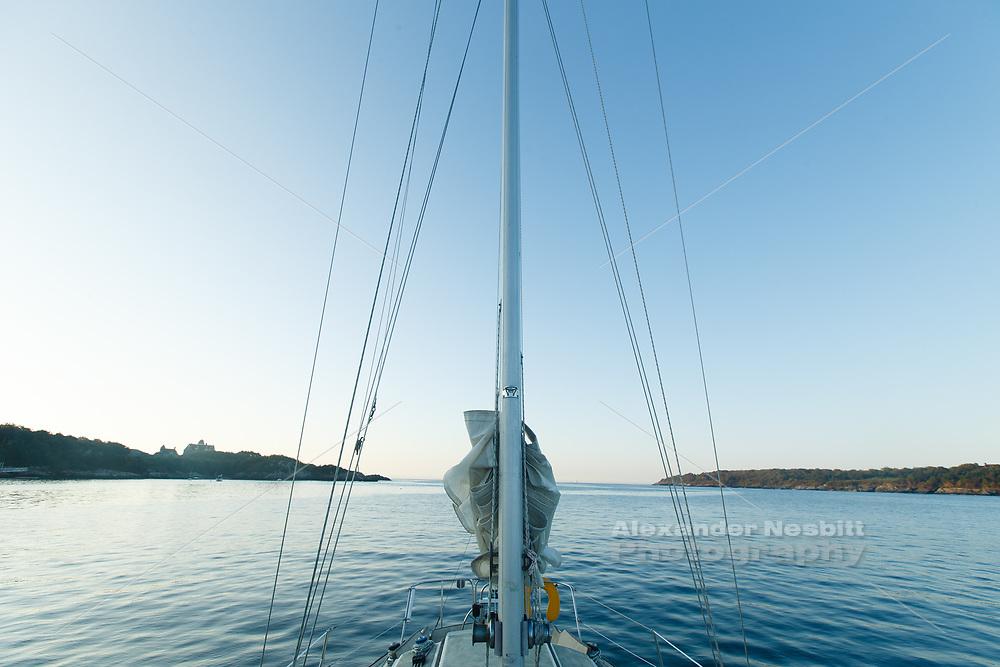 Jamestowm, RI - Yacht's mast slipots the gap out ot the sea.  Anchored at sunrise in Mackrell Cove