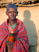 Maasai tribeswoman holding traditional milk gourd, Oyaratta village near Maasai Mara National Reserve, Kenya