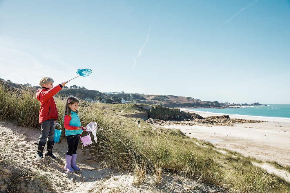 A boy and girl carrying buckets and nets, walking through the sand dunes at St Ouen's Bay and looking out over the beach and sea in Jersey, CI