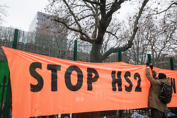 London, UK. 31 January, 2021. An anti-HS2 activist from umbrella campaign group HS2 Rebellion hangs a 'Stop HS2 Now' banner from fencing erected by HS2 Ltd around Euston Square Gardens. Climbers from the National Eviction Team (NET) are currently dismantling a camp built by activists, five of whom still occupying tunnels beneath the camp, in order to seek to protect trees from felling by HS2 Ltd in connection with the controversial HS2 high-speed rail project.