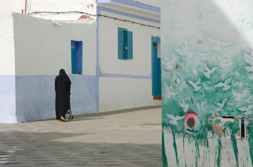 A local woman walks through medina, Asilah Morocco