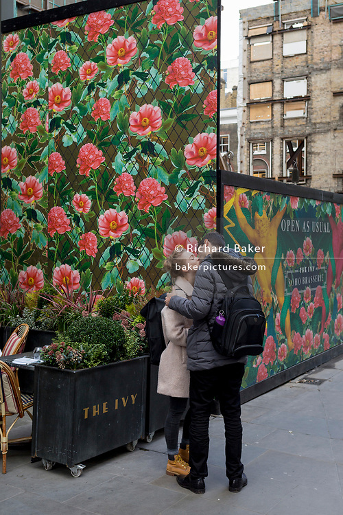 A kissing couple in front of temporary construction hoarding in a West End street, on 7th March 2019, in London, England.