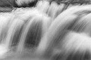 A long exposure close up of the main section of waterfalls of Donloup Creek reveals a silk curtain of water descending from a ledge of rocks that form the creek bed.