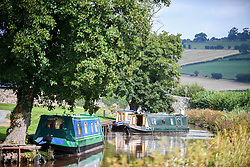 © Licensed to London News Pictures. 04/09/2021. Brecon, UK. An idyllic scene as a barge maneuvers on the Monmouthshire and Brecon Canal in South Wales on a beautiful Saturday afternoon as people enjoy the late Summer weather across the UK. Photo credit: Robert Melen/LNP