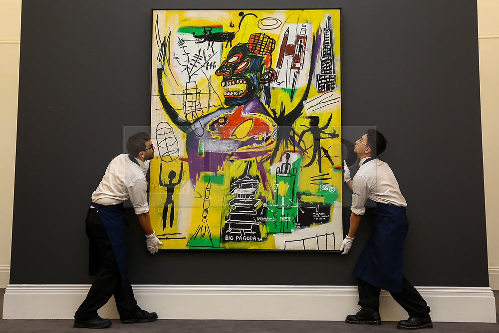 """© Licensed to London News Pictures. 27/09/2019. London, UK. Technicians hold Jean-Michel Basquiat's artwork titled """"Pyro"""" during the preview of Sotheby's Frieze Week Contemporary Art Sale. The auction will take place on 3rd October 2019.  Photo credit: Dinendra Haria/LNP"""