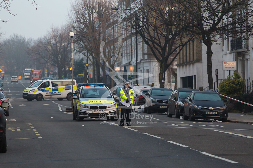 Police man a cordon surrounding the scene on Malden Road where a man was stabbed to death. Camden, London, February 21 2018.