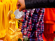 """29 APRIL 2017 - MINNEAPOLIS, MINNESOTA: A woman bathes a statue of the Buddha at Songkran Uptown. Several thousand people attended Songkran Uptown on Hennepin Ave in Minneapolis for the city's first celebration of Songkran, the traditional Thai New Year. Events included a Thai parade, a performance of the Ramakien (the Thai version of the Indian Ramayana), a """"Ladyboy"""" (drag queen) show, and Thai street food.     PHOTO BY JACK KURTZ"""