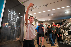 """© Licensed to London News Pictures; 23/08/2021; Bristol, UK. Young people from the Broad Plain Riverside Youth Project view and takes selfies of Banksy's """"Mobile Lovers"""" at the Vanguard Bristol Street Art: The Evolution of a Global Movement exhibition at M Shed. In 2014, Banksy painted Mobile Lovers on Clement Street near to the youth club and donated the piece to the club to raise funds to save it from closure. Broad Plain's young people have since created their own version of Mobile Lovers at the youth club, but the tour of Vanguard Bristol Street Art on Monday will be the first time that many of the young people have seen the original piece. Broad Plain Riverside Youth Project is an incredible resource for the city, providing opportunities through art and sport for youth from some of the most deprived areas of Bristol. The youth club has a long history of support from Bristol's street art community. The Vanguard team is made up of a collective of artists, specialists and collectors involved in the global street art movement. Photo credit: Simon Chapman/LNP."""