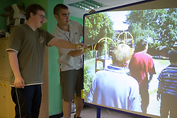 Boy with learning disability and teacher using interactive whiteboard,