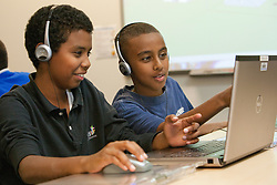 United States, Washington, Seattle, boys using laptop with headphones at after-school technology class.  Technology Access Foundation.