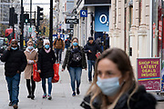 Asthe national lockdown ends and the new three tier system of local coronavirus restrictions begins, shoppers head out to Oxford Street to catch up on shopping as non-essential shops are allowed to reopen on 2nd December 2020 in London, United Kingdom. Many shoppers wear face masks outside on the street as a precaution as there are so many people around.