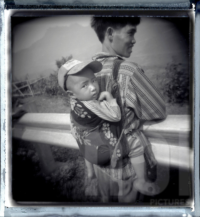 Portrait of a smiling father carrying his child in his back