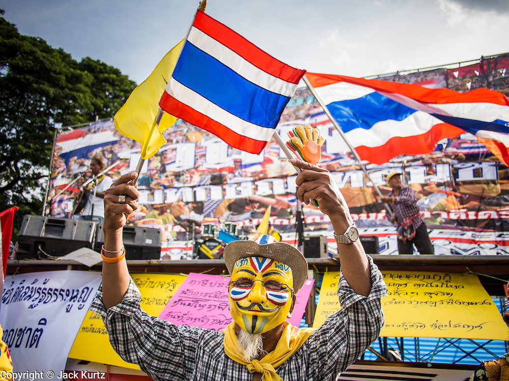 05 AUGUST 2013 - BANGKOK, THAILAND: An Anti-government protestor waves the Thai national flag and the flag of the Thai monarchy during an anti-government protest in Bangkok. About 500 people, members of the  People's Army against Thaksin Regime, a new anti-government group, protested in Lumpini Park in central Bangkok. The protest was peaceful but more militant protests are expected later in the week when the Parliament is expected to debate an amnesty bill which could allow Thaksin Shinawatra, the exiled former Prime Minister, to return to Thailand.    PHOTO BY JACK KURTZ