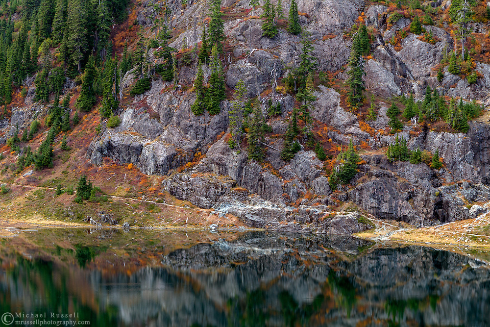 Fall foliage and the Chain Lakes Trail below Mount Herman reflect in the water of Bagley Lakes.   Photographed in Otober from the Fire and Ice Trail in the Heather Meadows Recreation area of the Mount Baker-Snoqualmie National Forest, Washington State, USA.