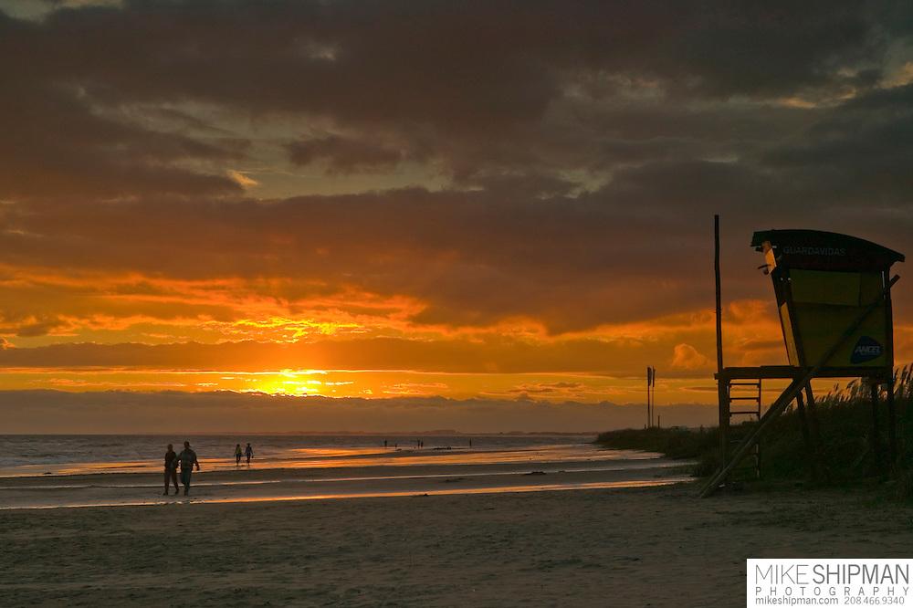 A couple walks on the beach by a lifeguard station at sunset, Playa Solari, La Paloma, Uruguay, South America