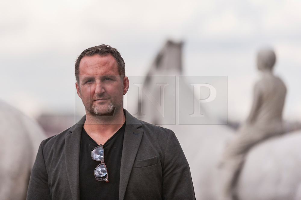 """© Licensed to London News Pictures. 02/09/2015 London, UK. The art installation entitled """"The Rising Tide"""" (comprising four horse-riders on horses with petroleum pumps for heads) by the underwater eco-sculptor Jason deCaires Taylor (pictured), stands on the foreshore of the River Thames in Vauxhall and is revealed with each low tide.  The installation aims to question man's reliance on fossil fuels and is part of this year's Totally Thames festival. Photo credit : Stephen Chung/LNP"""