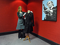 © Licensed to London News Pictures. 08/12/2011, London, UK. A Bonhams employee holds a coat worn by Michael Cain in the film Get Carter. The coat is expected to fetch 3500-4500 GBP. The painting on the wall is by Mark Fuller and is expected to fetch 600-750 GBP.   Bonhams, London, photocall for entertainment memorabilia today, 8th December 2011. The auction takes place on Thursday 15th DecemberPhoto credit : Stephen Simpson/LNP