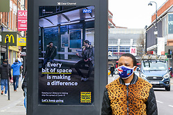 © Licensed to London News Pictures. 23/03/2021. London, UK. A man wearing a protective face covering walks past the government's 'Every bit of space is making a difference' poster in north London on the anniversary of the first Covid-19 lockdown in the UK. The next key date for restrictions easing is Monday 29 March 2021, when the 'Stay at Home' guidance will be dropped. Photo credit: Dinendra Haria/LNP