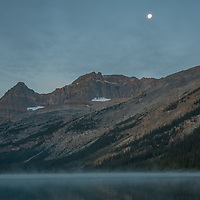 Photographers wait for dawn as the moon sets over Mount Thompson and misty Bow Lake in Banff National Park, Alberta, Canada.