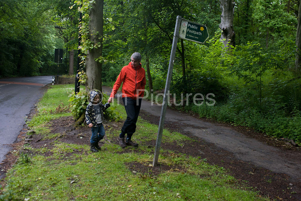 A father and son walk across a verge in woods south of Sheffield, England UK. Dad and son make their way across the road and on to the grass verge where they rejoin a footpath and the way home. Beech trees are in the background, green from recent rain. It is a Sunday and a time for fathers to take their children out for muddy walks to tire them out.