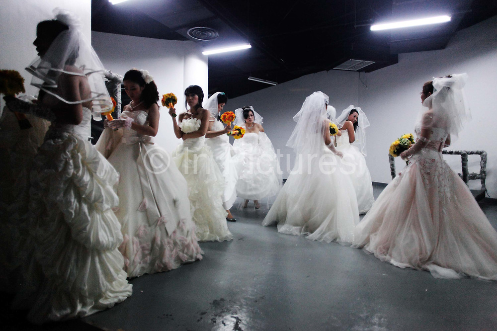 Newly weds participate in a group wedding held at one of the World Expo venues in Shanghai, China, on 23 September, 2010. With the country's sex ratio skewed towards more men as a result of the one child policy and the Chinese traditional preference for boys, Chinese men are increasingly having difficulty to find suitable brides.