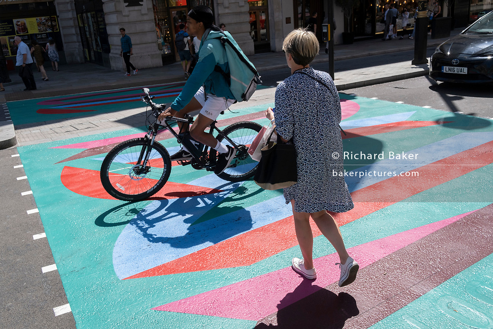 As a young cyclist pedals past, a woman crosses the multi-coloured markings of a crossing at the junction of Piccadilly and Piccadilly Circus, on 16th July 2021, in London, England.