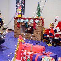 Garick Soseeah poses with Santa Claus as lincoln Soseeah and Lenee Kaskalla take photos during the Toys for Tots event at the Zuni Wellness Center in Zuni Thursday.