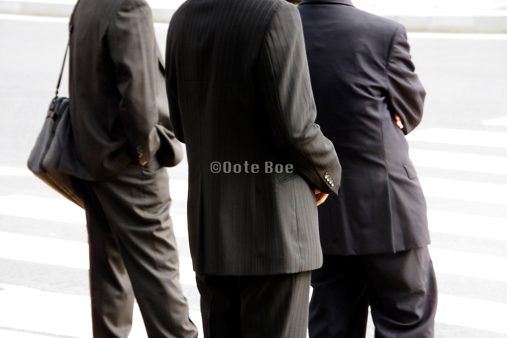 young businesspeople standing and waiting at a pedestrian crossing