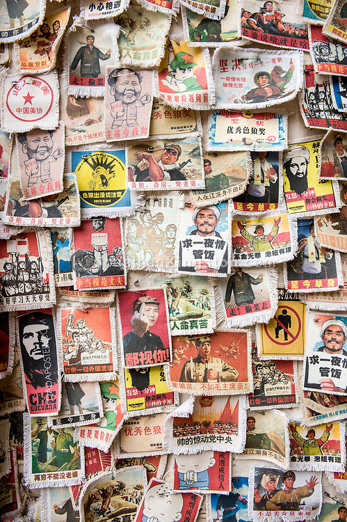A wall of cloth patches with pictures and political slogans written in chinese in Yangshuo, China.