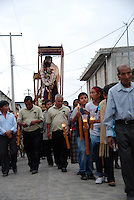 """Mexico, Oaxaca, Teotitlan del Valle, April 18, 2011. On a moody Monday in southern Mexico, the Zapotec townspeople of Oaxaca's Teotitlan del Valle reenact all fourteen Stations of the Cross through this mountain community's winding cobblestone streets. From the first station, where Jesus is condemned to die, to the last, where he is laid in his tomb, somber processions accompanied by flowers, singers and a brass band stop at each refuge, adorned with """"tapetes"""" created by master carpet weavers and blessed with food and drink for all. Multimedia and more at www.mexicoculturalcalendar.com"""