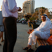 BEIRUT,LEBANON- MAY 2009 : A Saudi male tourist, wearing a traditional white dishdasha  relaxing  with other  persons in the Corniche in  front of Pigeon Rocks . 05/30/2009 .The Corniche is a walk  that borders on the city next to the sea where many Lebanese  and tourist are going to walk and to relax . Beirut, Lebanon.   ( Photo by Jordi Cami )