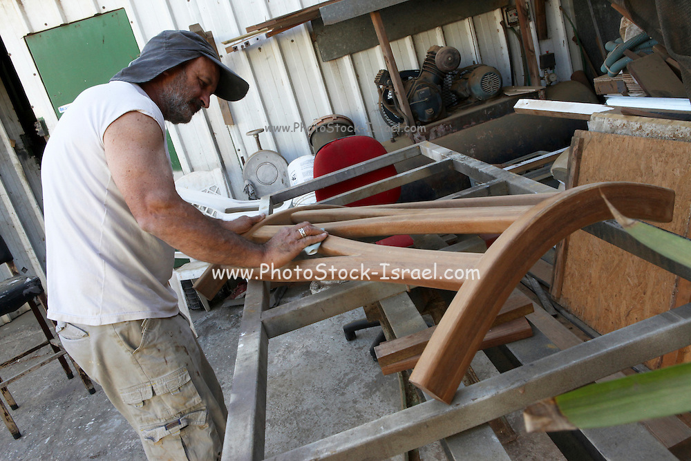 Carpenter Sandpapers a wooden chair back