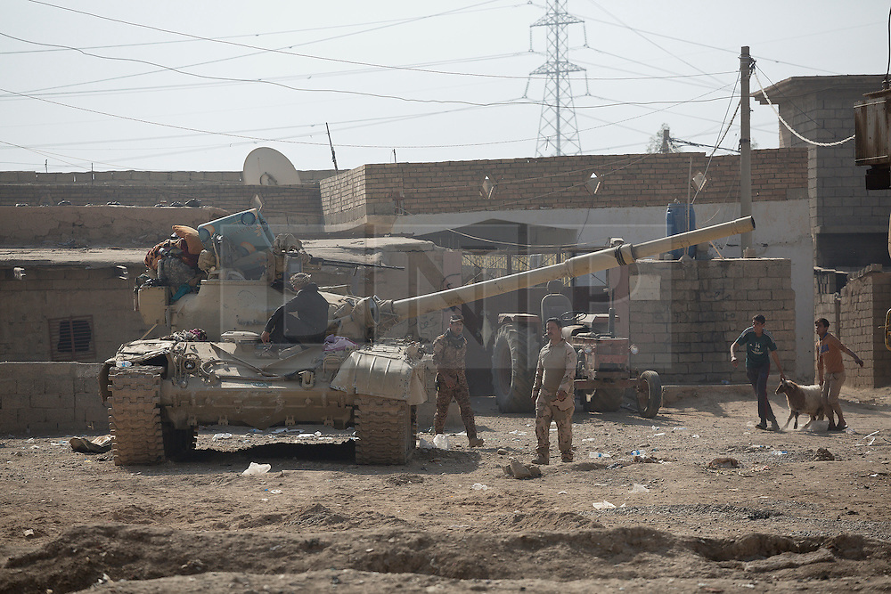 Licensed to London News Pictures. 11/11/2016. Mosul, Iraq. A T-72 tank, belonging to the Iraqi Army's 9th Armoured Division, wait in Mosul's Hay Intisar district on the south east of the city. The district was taken by Iraqi Security Forces (ISF) around a week ago and, despite its proximity to ongoing fighting between ISF and ISIS militants, many residents still live in the settlement.<br /> <br /> The battle to retake Mosul, which fell June 2014, started on the 16th of October 2016 with Iraqi Security Forces eventually reaching the city on the 1st of November. Since then elements of the Iraq Army and Police have succeeded in pushing into the city and retaking several neighbourhoods allowing civilians living there to be evacuated - though many more remain trapped within Mosul.  Photo credit: Matt Cetti-Roberts/LNP