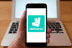 Using iPhone smartphone to display logo of Deliveroo home takeaway food delivery service